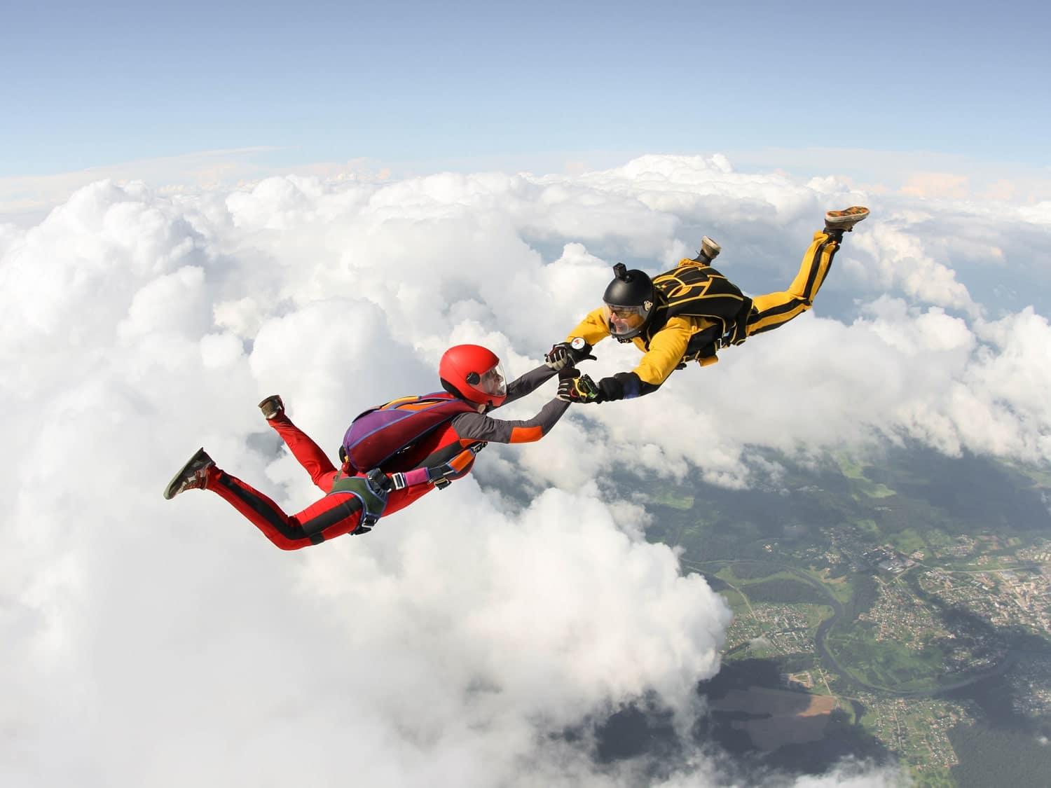 Two people while skydiving above the clouds